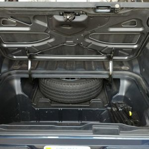 Full-size spare tire in service tray; tire is an OEM LTX M/S on an OEM 18 inch alloy rim