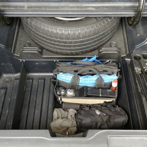 2009 RTL In-Bed Trunk with full-size spare and OEM Trunk Dividers holding back an air compressor, rags, and a tool bag that contains many essentials,